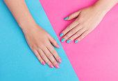 背景にピンクの爪にマニキュアを持つ若い女性の手のクローズ アップ