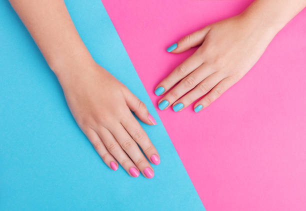 Closeup of hands of a young woman with manicure on nails against pink background stock photo
