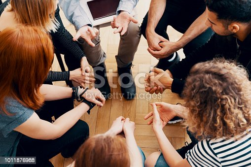 istock Close-up of hands of teenagers sitting in a circle during a support meeting 1011876988
