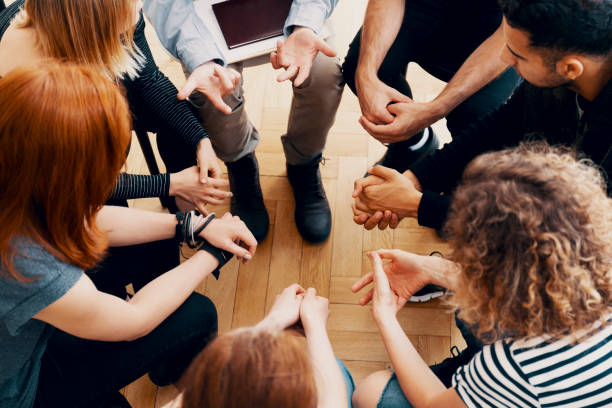 close-up of hands of teenagers sitting in a circle during a support meeting - teen counseling stock photos and pictures