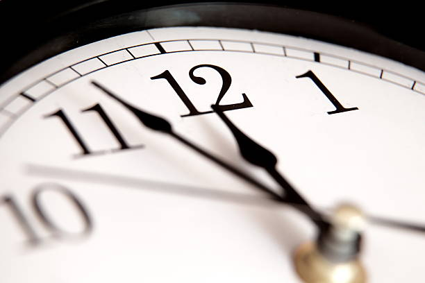 closeup of hands on clock face - countdown stock photos and pictures
