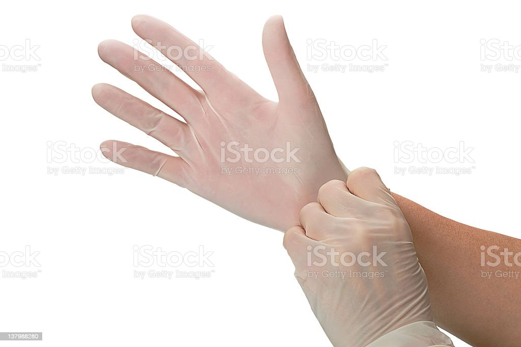 Close-up of hands putting on clear surgical gloves stock photo