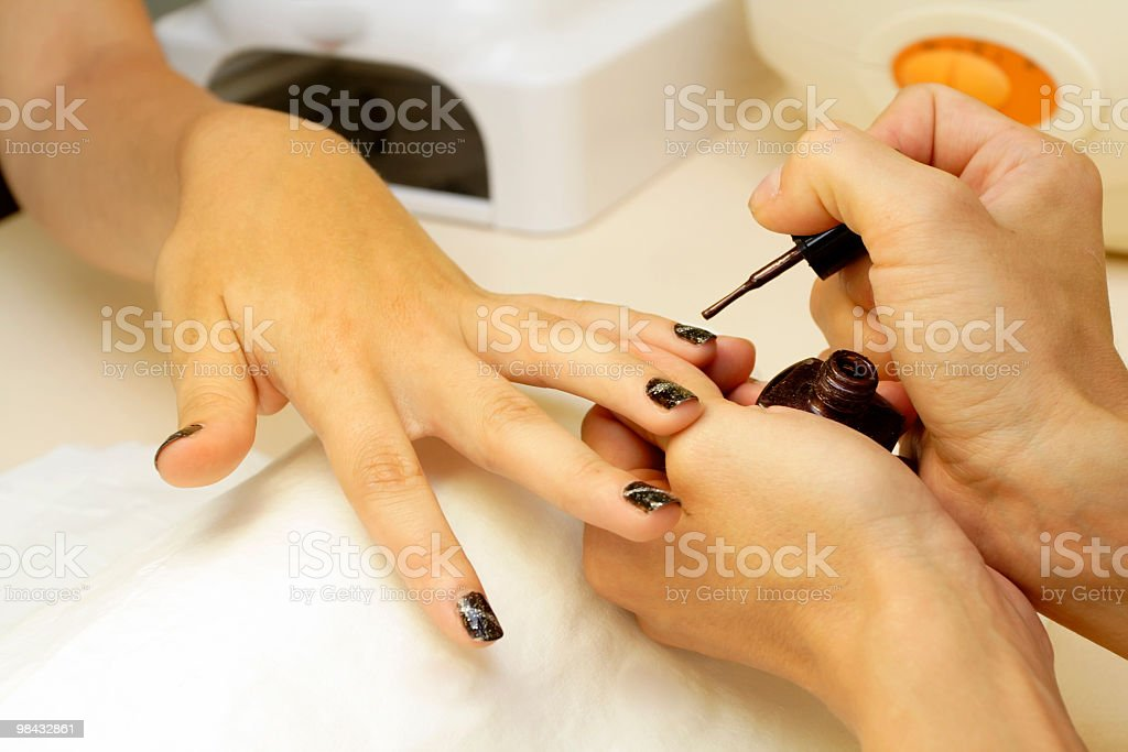 Close-up of hands receiving nail polish decoration royalty-free stock photo