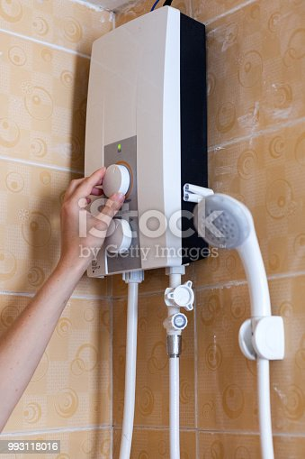 996279800istockphoto Close-up of hands setting the temperature of water in electric boiler in the shower room 993118016