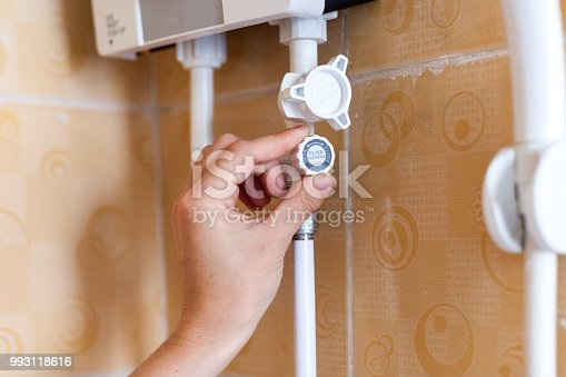 996279800istockphoto Close-up of hands setting the temperature of water in electric boiler in the shower room 993118616