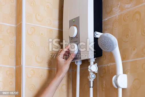 996279800istockphoto Close-up of hands setting the temperature of water in electric boiler in the shower room 993118702