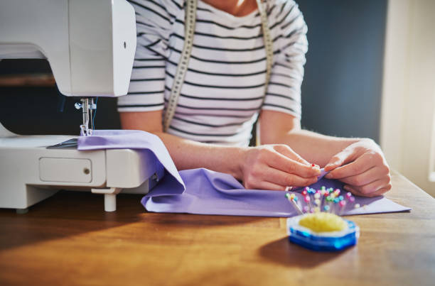 Closeup of hands sewing Closeup of hands sewing on a machine stitching stock pictures, royalty-free photos & images