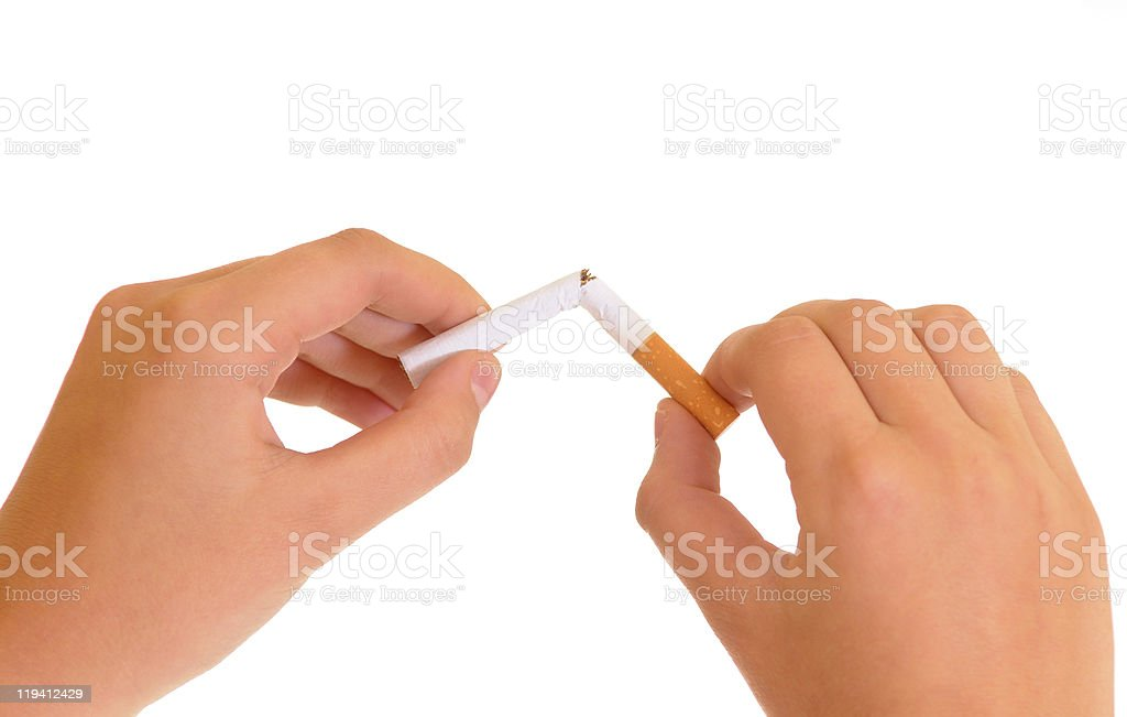 Closeup of hands snapping cigarette in half royalty-free stock photo