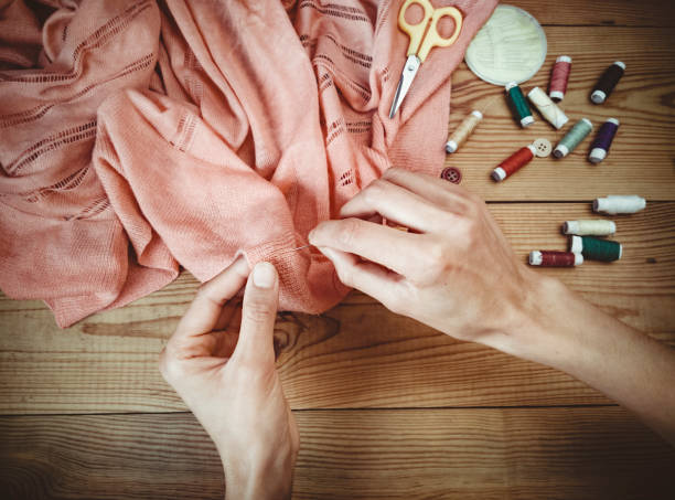 Close-up of hands stitch cloths. Indoor close-up of woman hands stitch cloths and other haberdashery pleased on wooden table. stitching stock pictures, royalty-free photos & images