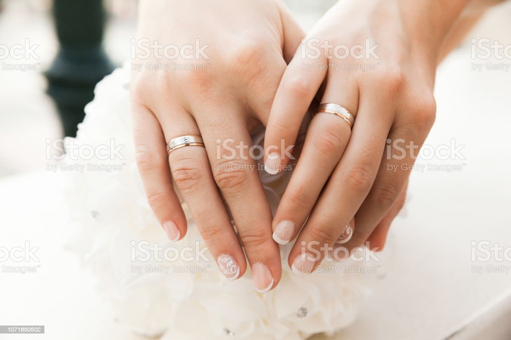 Closeup Of Hands With Wedding Rings Of Two Brides stock photo