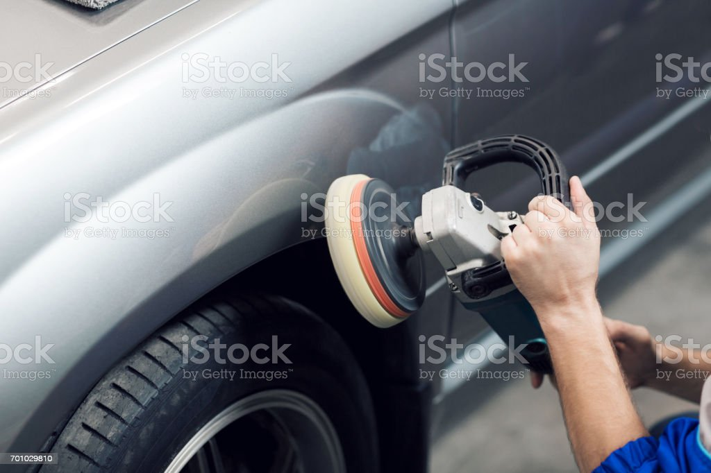 Close-up of hands worker using polisher to polish a gray car body in the workshop stock photo