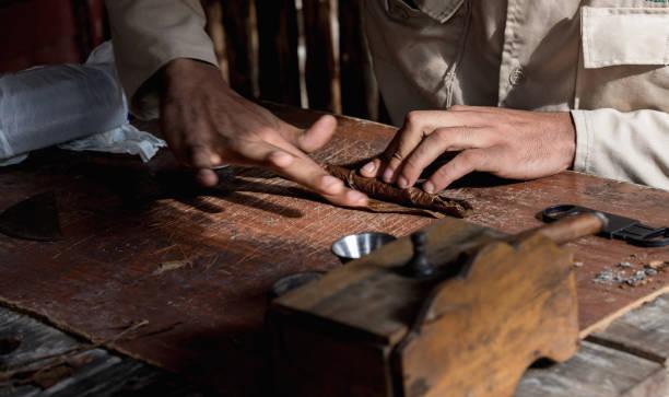 Nahaufnahme der Hände gewickelt aus den trockenen Tabak Blätter eine echte kubanische Zigarre. – Foto
