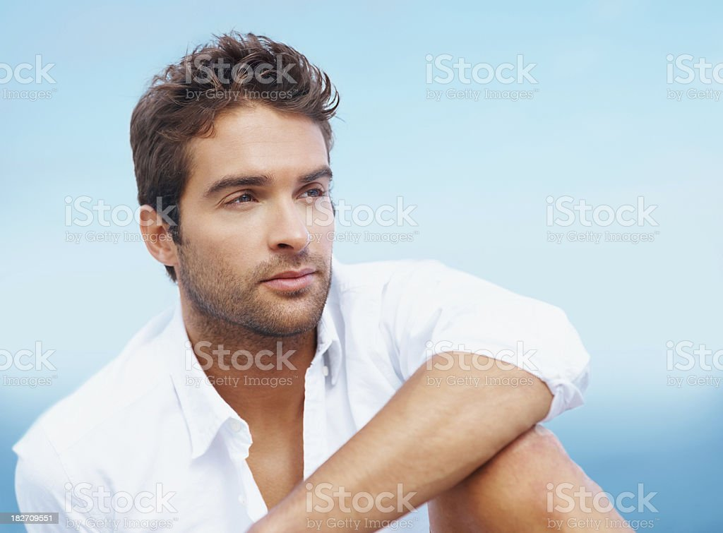 Close-up of handsome thoughtful man against sky royalty-free stock photo