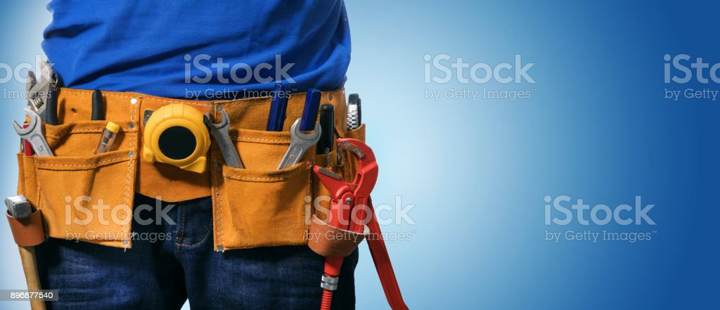 closeup of handyman tool belt on blue background with copy space stock photo