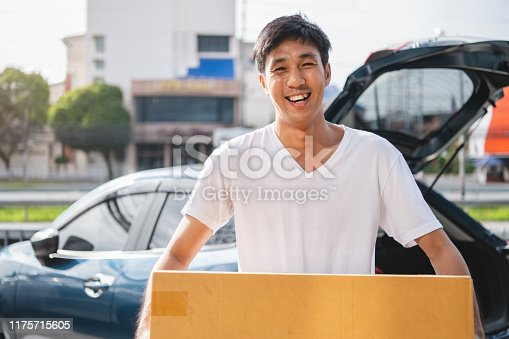istock Closeup of happy Asian man delivering cardboard box to customers via private car. People lifestyles and business occupation concept. Young male courier in casual clothes. Shipping and packaging 1175715605