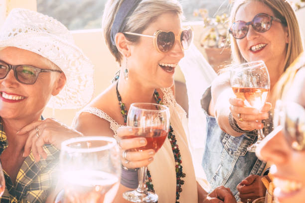 Closeup of happy beautiful cheerful people women celebrating together with red wine - bright sunny image joyful and friendship - young senior ladies smiling and laughing having fun at party stock photo