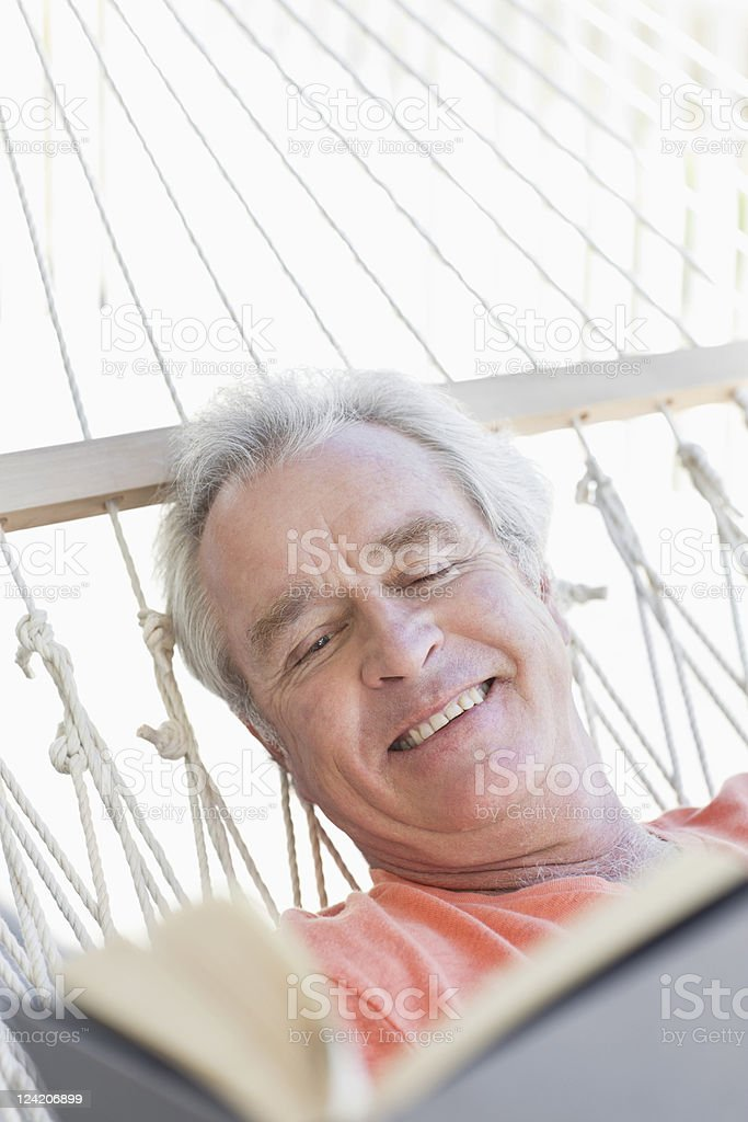 Close-up of happy senior man reading book in hammock royalty-free stock photo