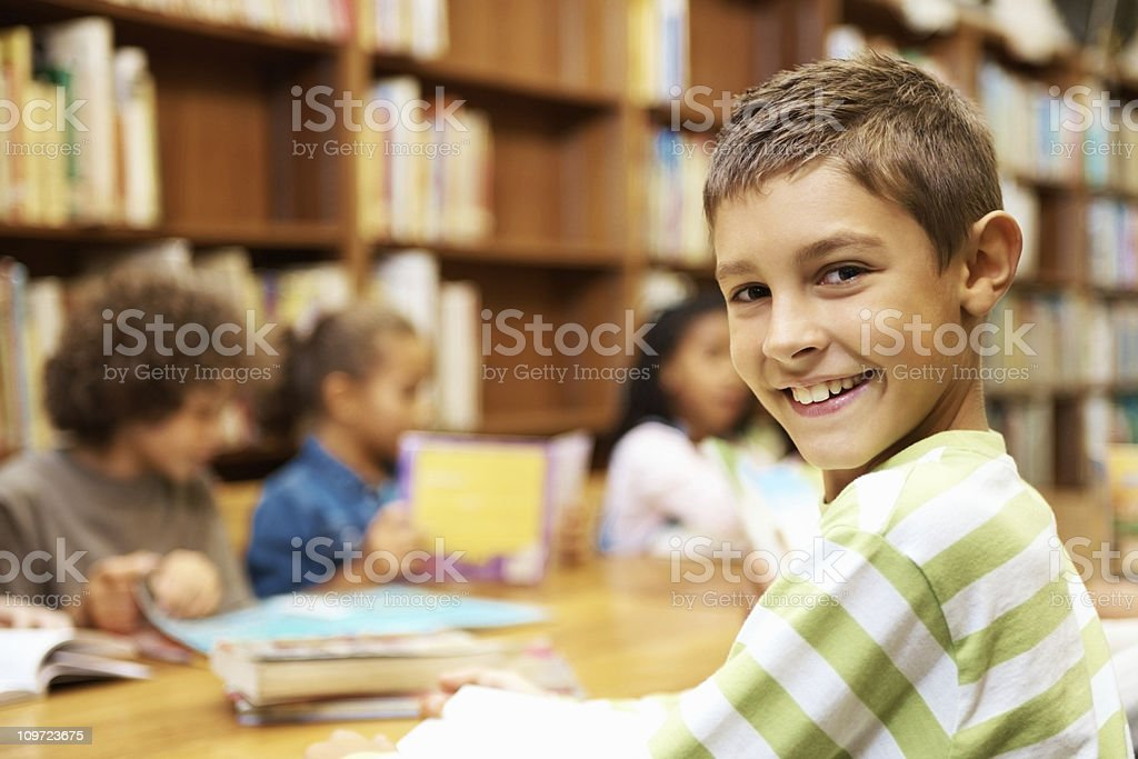 Closeup of happy student sitting in a school library royalty-free stock photo