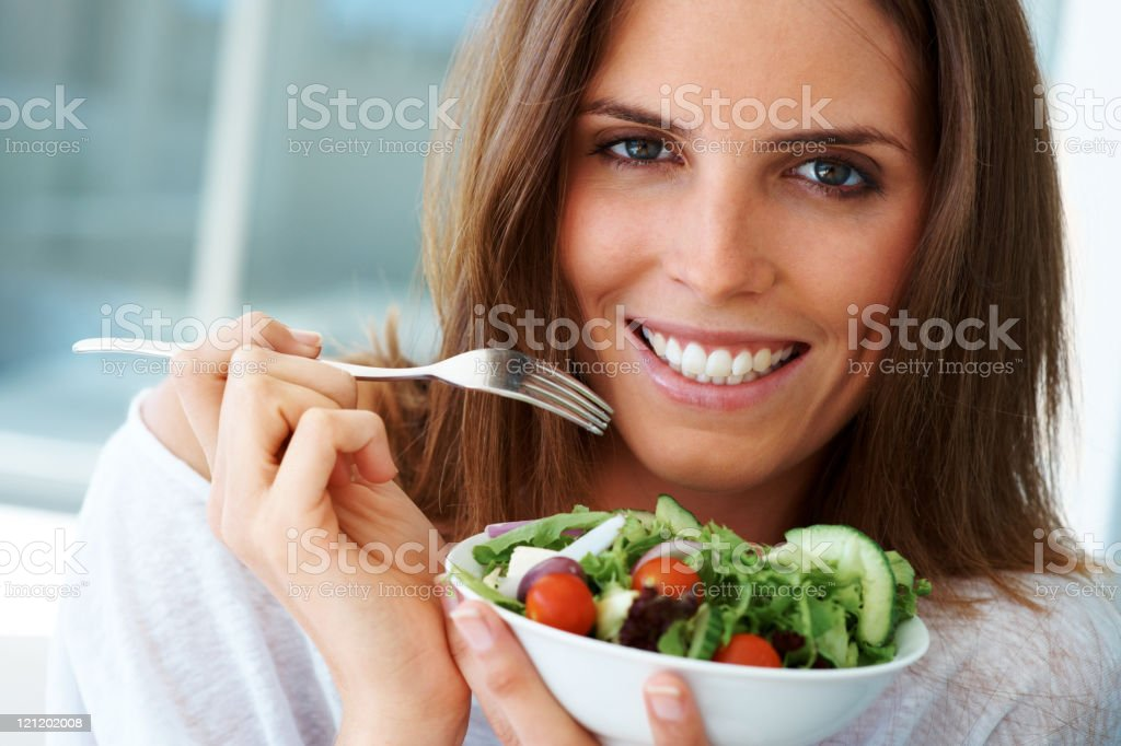 Close-up of happy woman eating vegetable salad royalty-free stock photo