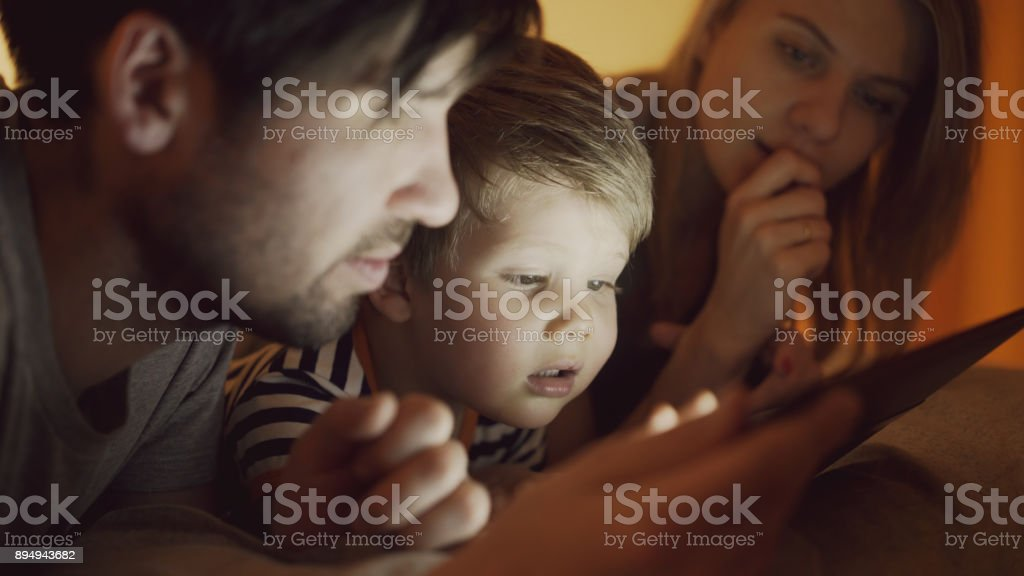Closeup of Happy young family lying in bed at home while little boy learning to play digital tablet computer before sleeping time stock photo