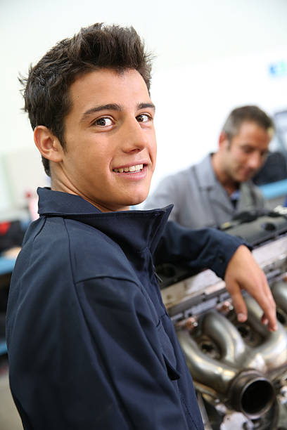 Closeup of happy young mechanic with blue dungarees stock photo