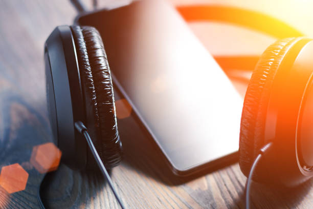 Close-up of headphones connected to a smart phone on a wooden background, listening to music, selective focus stock photo