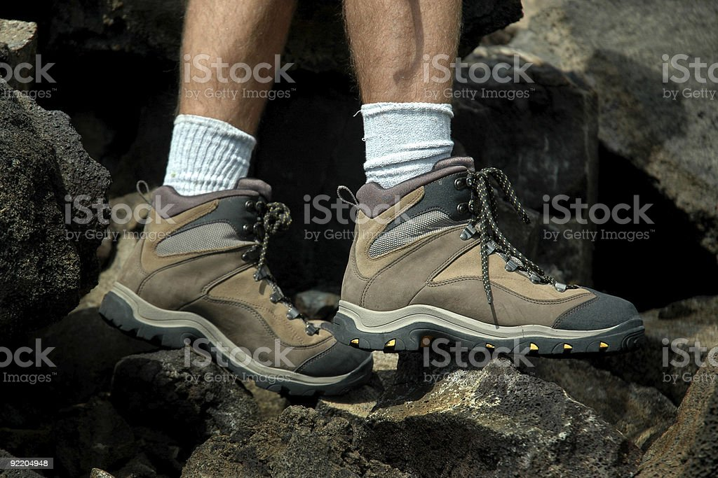 Close-up of hiker's boots stepping on rough rocks royalty-free stock photo