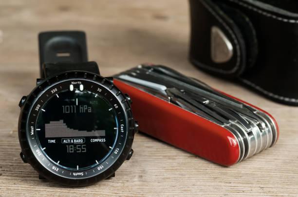 närbild av vandring arm band sur och mångsidig kniv på trä bord - barometer bildbanksfoton och bilder
