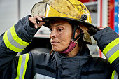 istock Close-up of Hispanic Female Firefighter Putting on Helmet 1313773513