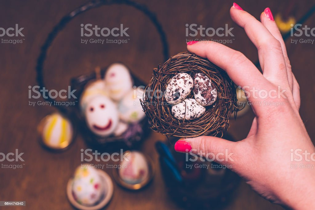 Close-up of holding little egg nest and decorating eggs for easter...