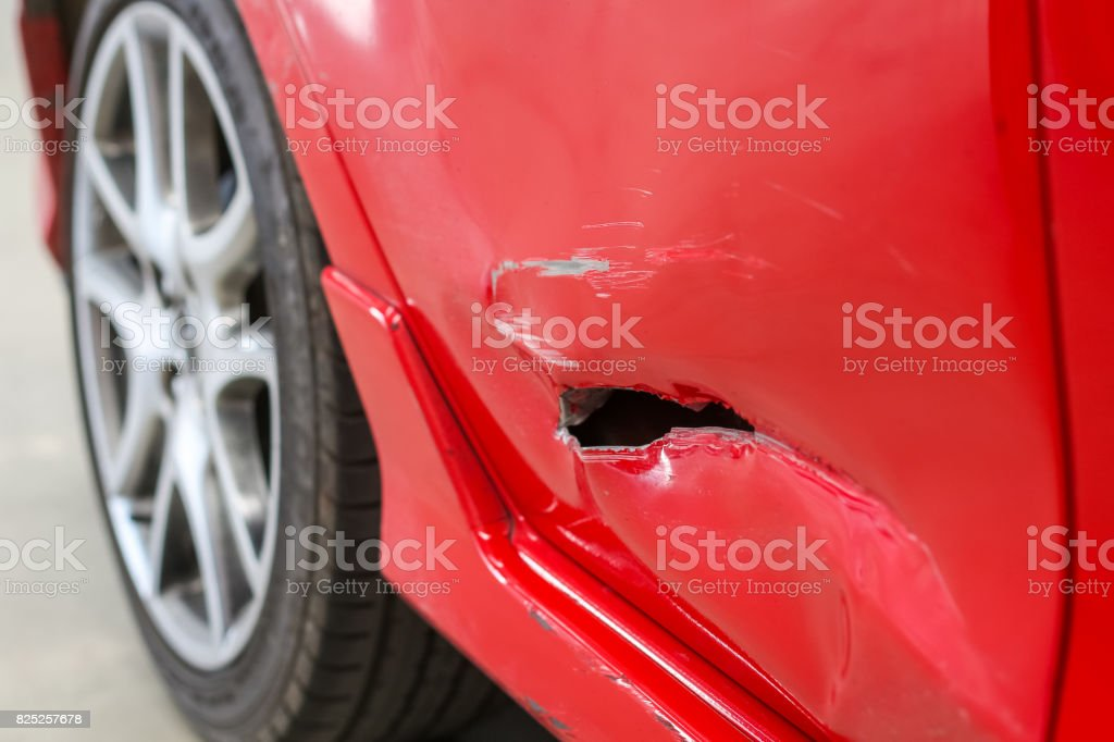 Closeup of hole accident in the side door of the red car stock photo