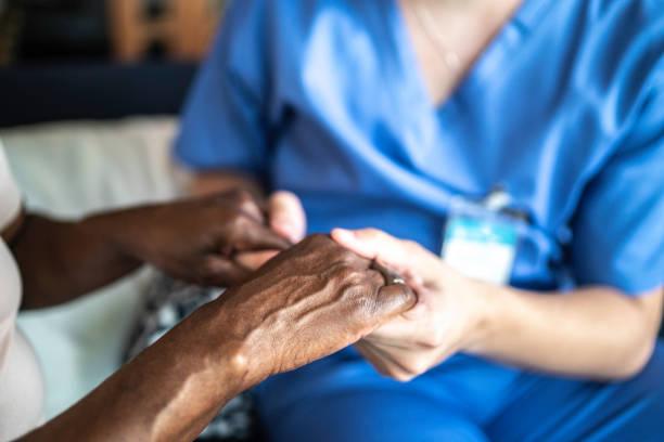 close-up van huis verzorger en senior vrouw die handen vasthoudt - dementia stockfoto's en -beelden