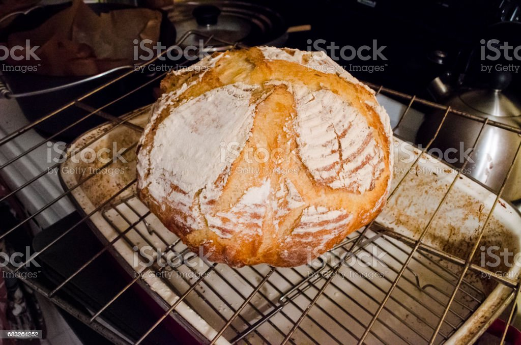Closeup of homemade sourdough bread round loaf on wire rack in kitchen with score marks foto de stock royalty-free