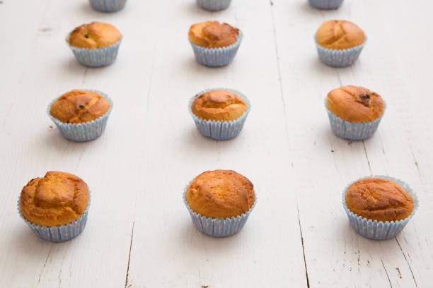 nahaufnahme der hausgemachte vanille muffins in blauem papier tassen in reihen auf weißem hintergrund aus holz. gesunder snack. - vanille muffins stock-fotos und bilder