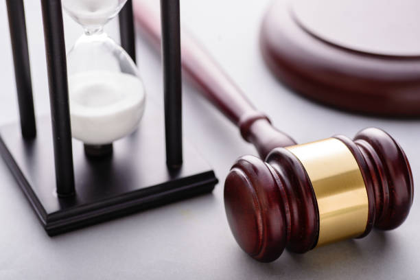 Close-up of hourglass and wooden auction gavel stock photo