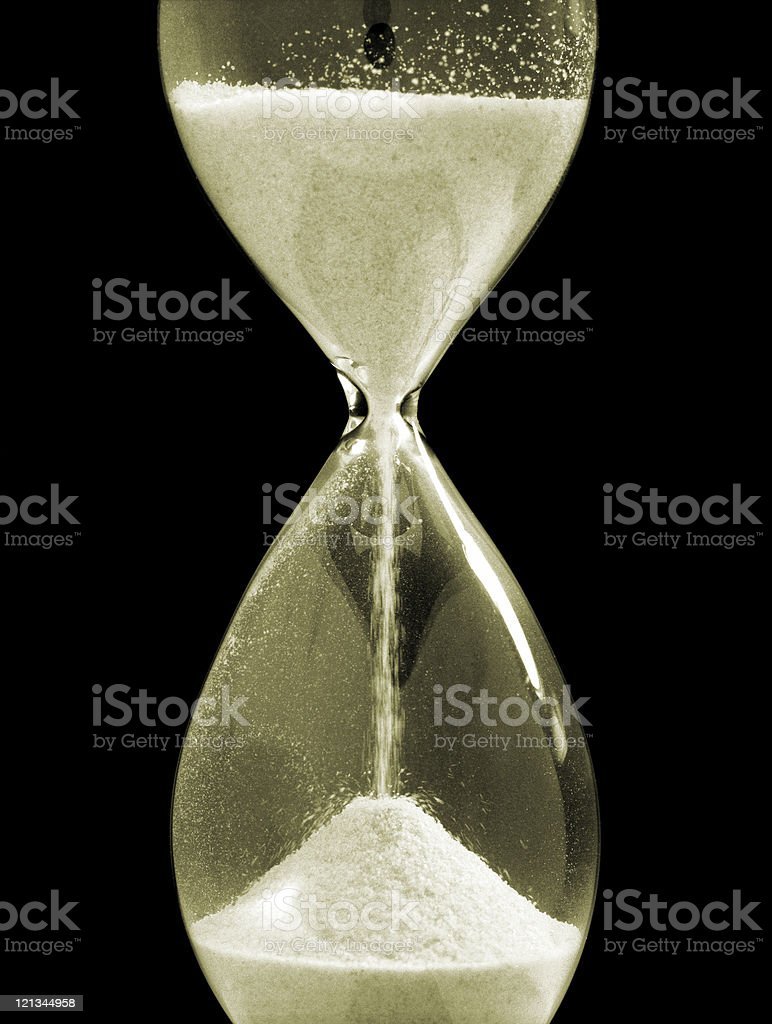 Close-up of hourglass with sand isolated on black, studio shot royalty-free stock photo