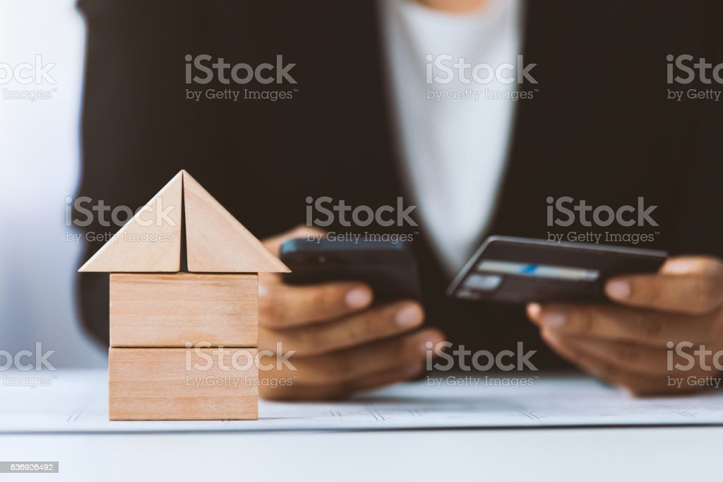 Close-up of house architectural model with businessperson holding credit card and using mobile above project house draw plan stock photo