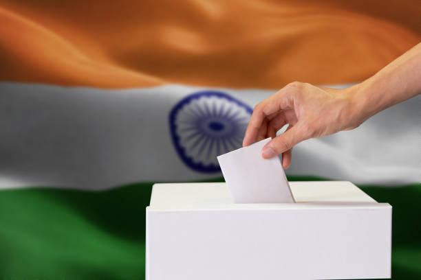 Nahaufnahme der menschlichen Hand gießen und einfügen eine Abstimmung und die Wahl eine Entscheidung treffen, was er will im Polling-Box mit Indien Flagge gemischt im Hintergrund. – Foto