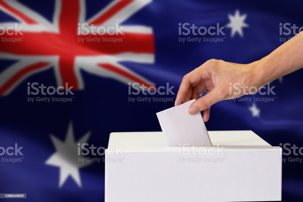 Close-up of human hand casting and inserting a vote and choosing and making a decision what he wants in polling box with Australia flag blended in background. royalty-free stock photo