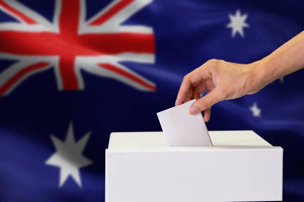 Nahaufnahme der menschlichen Hand Gießen einfügen eine Abstimmung und die Wahl und Entscheidung, was er will im Polling-Box mit Australien Flagge gemischt im Hintergrund. – Foto