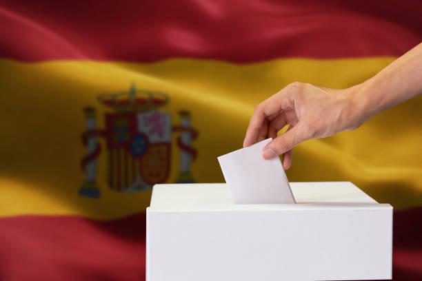 Nahaufnahme der menschlichen Hand Gießen einfügen eine Abstimmung und die Wahl und Entscheidung, was er will im Polling-Box mit Spanien Flagge gemischt im Hintergrund. – Foto