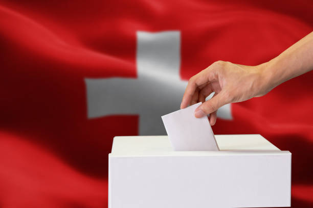 close-up of human hand casting and inserting a vote and choosing and making a decision what he wants in polling box with switzerland flag blended in background. - кандидат на пост президента стоковые фото и изображения