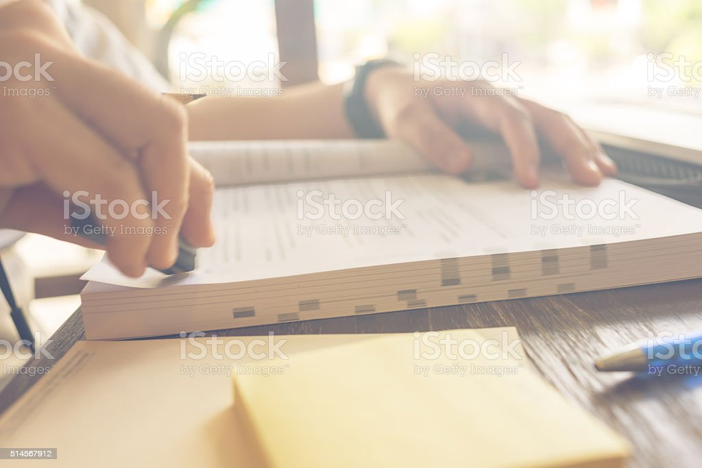 Close-up of human hand erasing notes on the book stock photo
