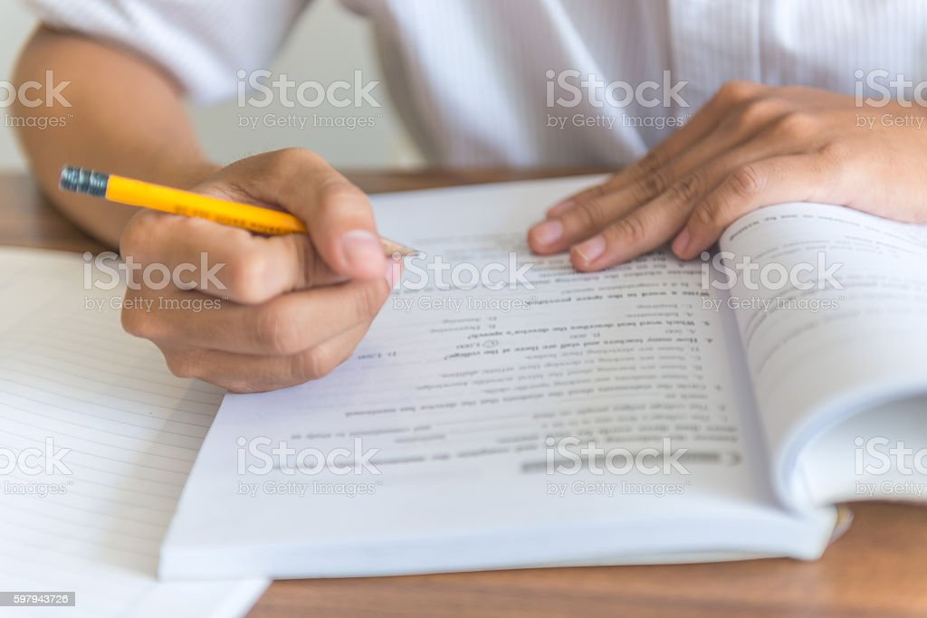 Close-up of human hand holding pencil taking note on book foto royalty-free