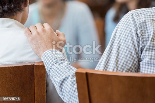 956725746 istock photo Closeup of human hand on unrecognizable person's shoulder 956725746