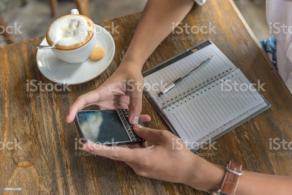 Close-up of human hand using smartphone and cappuccino beside stock photo
