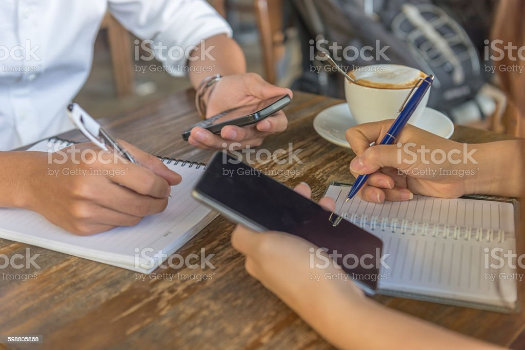 Close-up of human hand writing on notebook while using smartphone stock photo