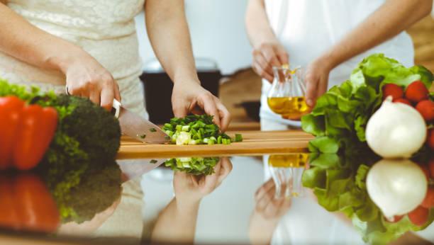 Nahaufnahme von menschlichen Händen Kochen in der Küche. Mutter und Tochter oder zwei Freundinnen schneiden Gemüse für frischen Salat. Freundschaft, Familienessen und Lifestyle-Konzepte – Foto