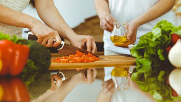 крупным планом человеческих рук приготовления пищи на кухне. мать и дочь или две подруги резки овощи для свежего салата. концепция дружбы, с - class стоковые фото и изображения