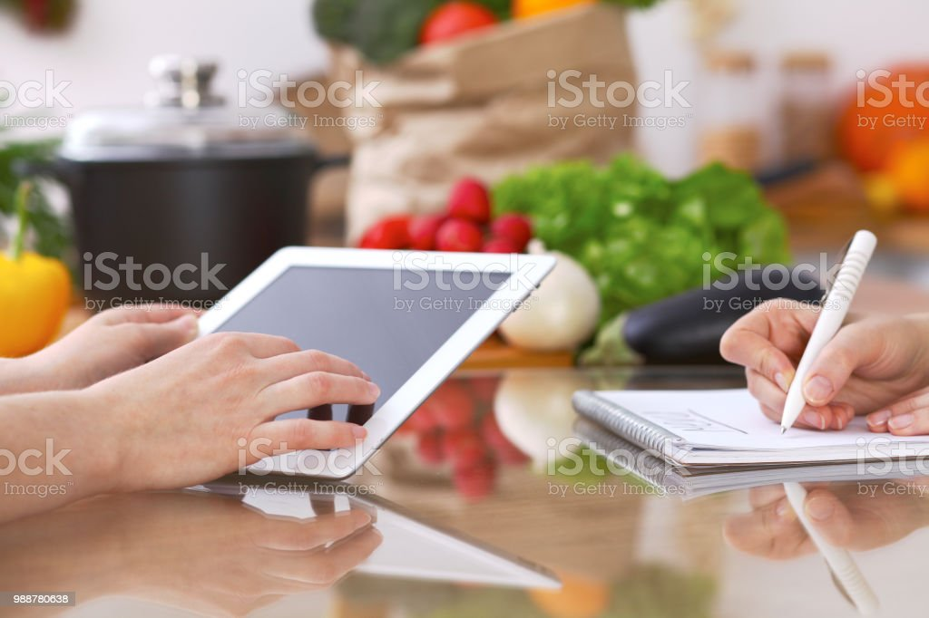 Closeup of human hands cooking in kitchen using touch pad. Women...